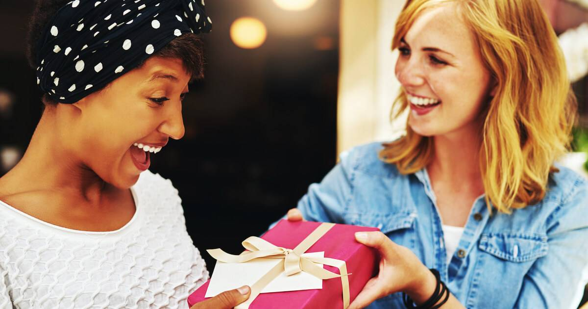 Photo of woman giving a gift to her female friend. money-saving gifts pbs rewire
