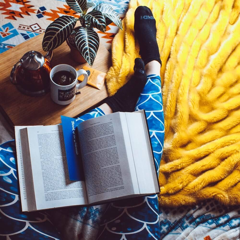 Person reading and drinking tea on yellow rug Indie Book Stores pbs rewire