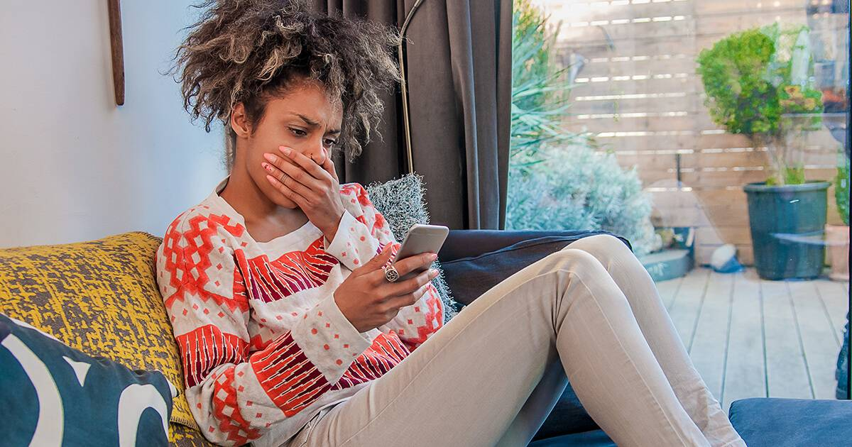 Woman holding phone, covering her mouth in shock. Rewire PBS Work Financial adviser