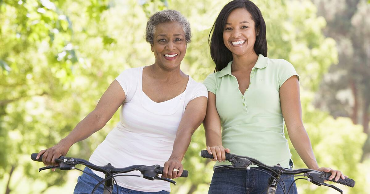 Two women on bikes outdoors smiling. Rewire PBS Love Mother's