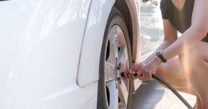 Woman filling her car tires with air Car Care pbs rewire