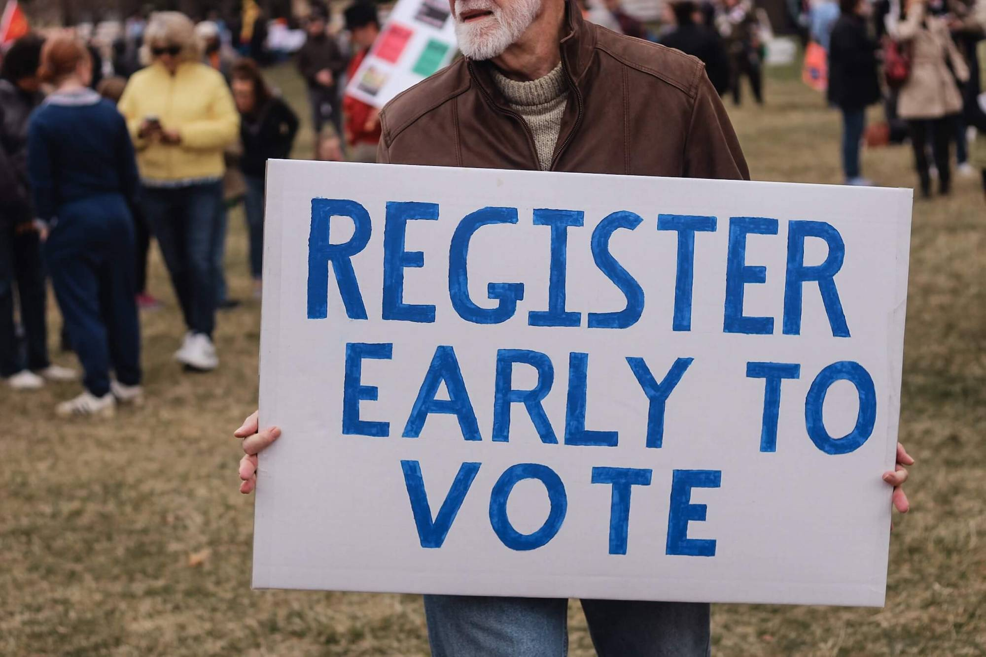 "Man holding ""Register Early to Vote"" sign Voting pbs rewire"