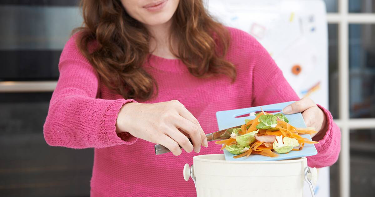 Woman Scraping Vegetable Peelings Into Recycling Bin. Rewire PBS Our Future Composting
