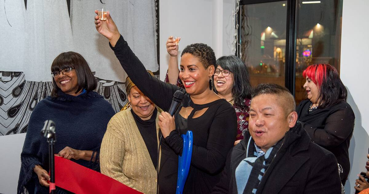 Raeisha Williams raises a glass of champagne and holds giant scissors at the grand opening ceremony for a tea house. Rewire PBS Living Heritage Tea House