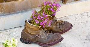 A pair of old used boots up cycled as flower pots. Decorate Sustainably pbs rewire