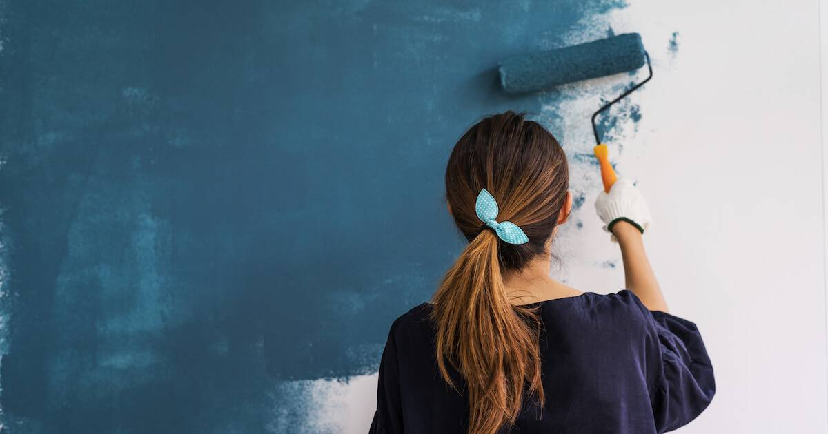Young happy woman painting interior wall. Decorate Sustainably pbs rewire