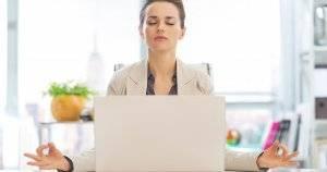 Business woman meditating near laptop. Mental Health pbs rewire