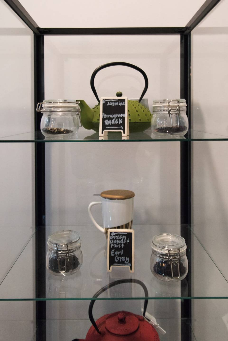 A display of tea pots and loose leaf tea on glass shelves. Rewire PBS Living Heritage Tea House
