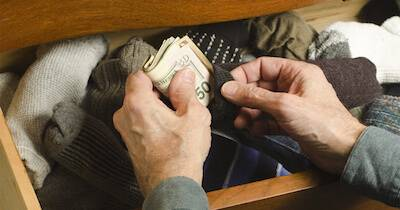 Man putting some cash into his sock drawer. Financially Fit pbs rewire
