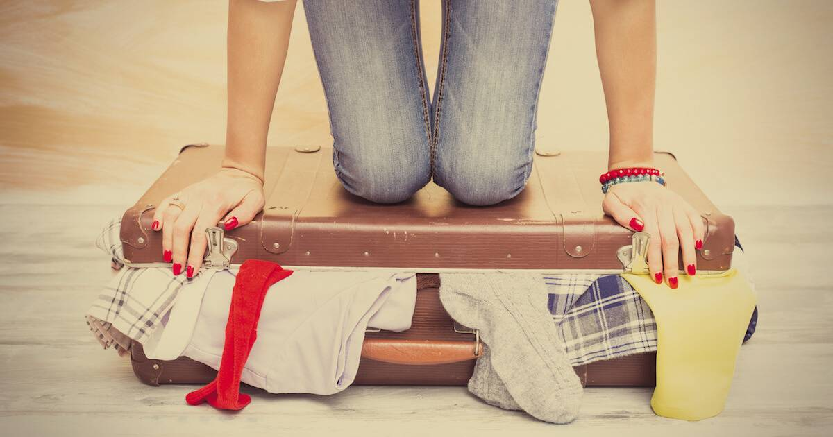 Woman trying to close a suitcase. Budget Airline pbs rewire