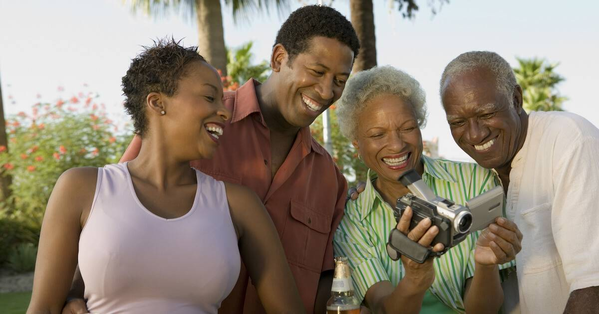 African-American couple looking at parent's camcorder. Vacation with In-Laws pbs rewire