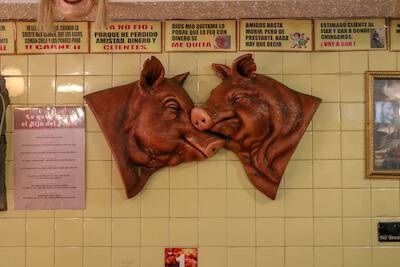 Two pigs decorate the wall inside Las Carnitas Uruapan. Rewire PBS Living Mexican