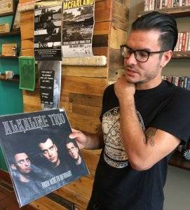 One of the founders of Caydence Records & Coffee showing off some vinyl. pbs rewire