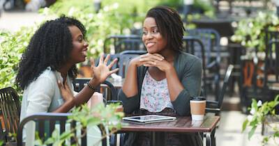 African-American woman telling story to her female friend. FOMO pbs rewire