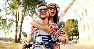 Man and woman enjoying a ride on a moped. Self-Care pbs rewire