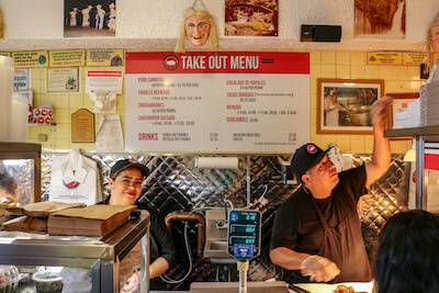 Two servers chop carnitas and package to-go orders inside Carnitas Uruapan, a Mexican carnitas restaurant in Chicago. Rewire PBS Living Mexican
