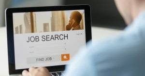 Monitor view over a male shoulder, job search title on the screen. Hiring Trends pbs rewire
