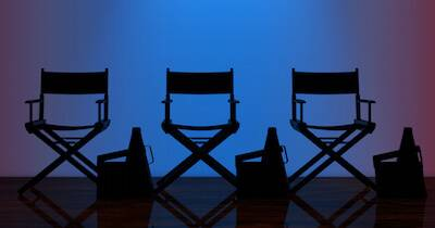 Three director's chairs sit empty on a stage in front of blue lights. Film Festivals pbs rewire