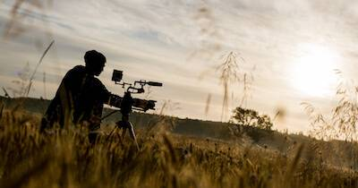Filmmaker setting up their camera for the perfect shot in an open field while the sun sets. Film Festivals pbs rewire