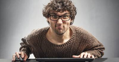 Male bully looking at his computer screen while typing on his keyboard. True Threat pbs rewire