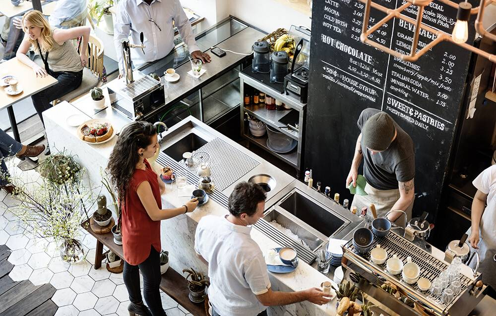 A coffee shop interior as seen from above. Two people stand at the counter, a barista preps something on the other side. Rewire PBS Our Future Positivity