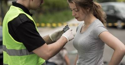 Woman being given a breathalyzer test by a police officer after a car crash. Warrant pbs rewire