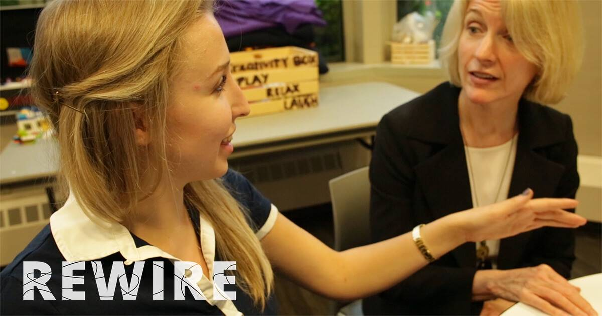 A young woman talks with a professional woman at a table. Rewire PBS Work ExpressionMed