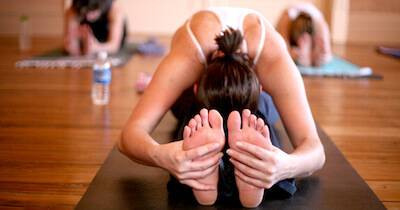 Woman touching her feet in a yoga pose. Best Yoga pbs rewire