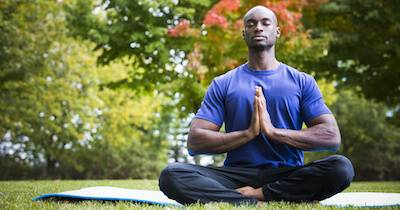 African-American man practicing yoga in a park. Best Yoga pbs rewire