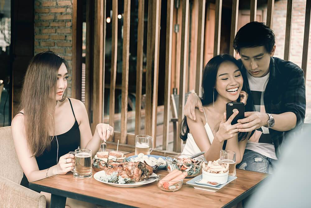 An asian single woman looks on at a young asian couple with disgust. Rewire PBS Love Bad Relationship.