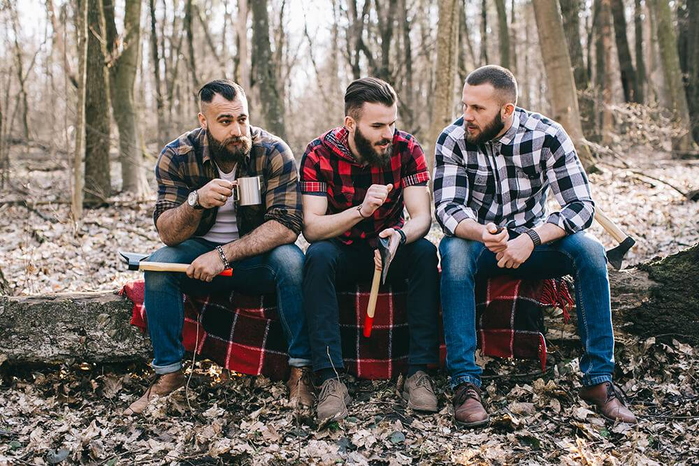 Three men in plaid sit on a plaid blanket in the forest, holding hand axes and coffee. Rewire PBS Love Bad Relationship