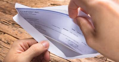 Person opening their paycheck and looking inside the envelope. How much money pbs rewire