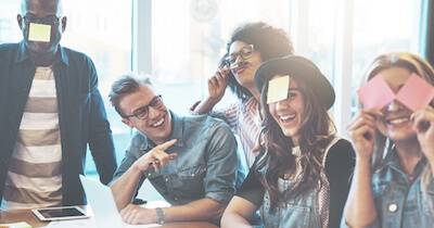 Group of young office workers pointing and laughing at those with post-it notes on their face. Workplace Attire pbs rewire