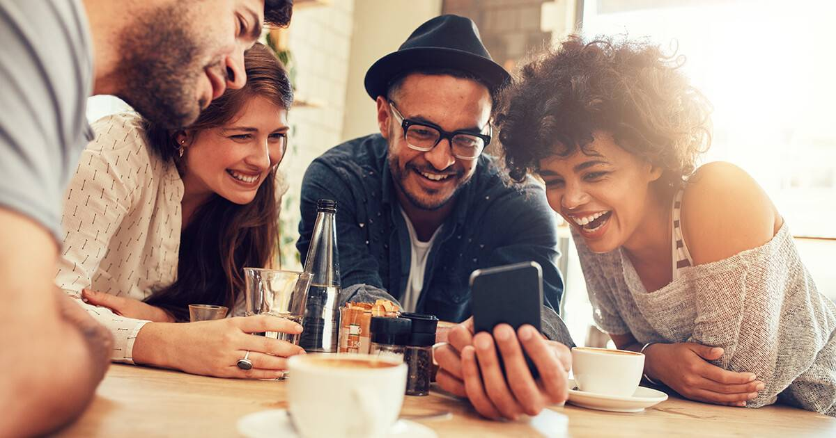 Portrait of cheerful young friends looking at smart phone while sitting in cafe. Mixed race people sitting at a table in restaurant using mobile phone. Rewire PBS Our Future Get Offline