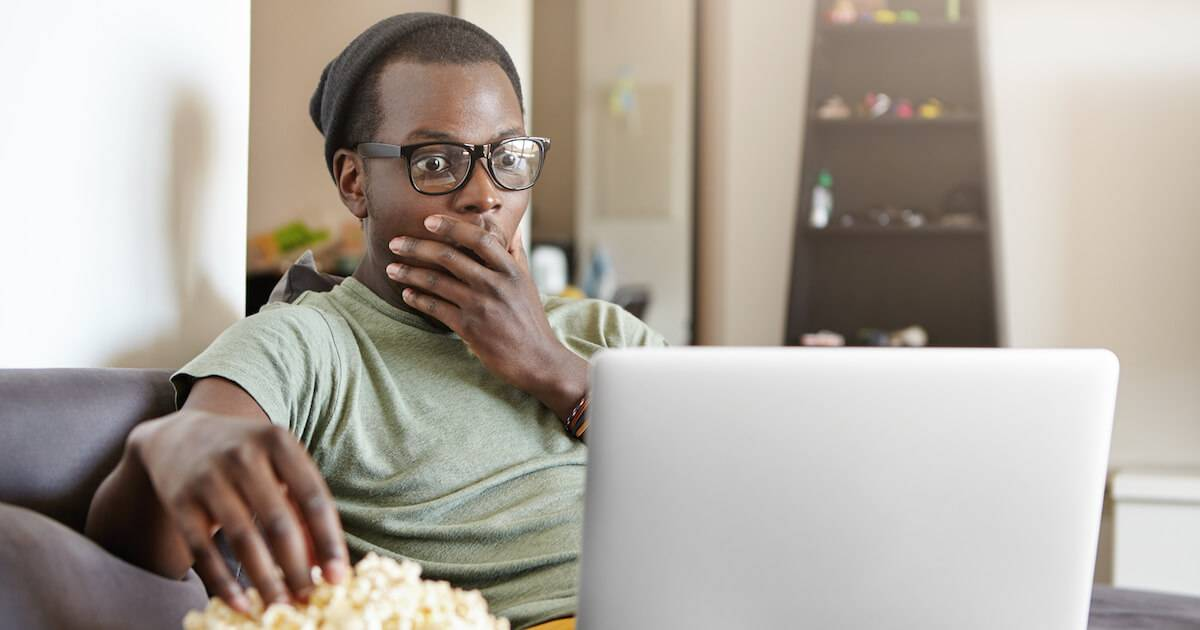 Young African-American man eating popcorn while he watches a movie on his laptop. Culturally Relevant Films pbs rewire