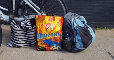 Two totes and a backpack next to a bicycle. Car-Free pbs rewire