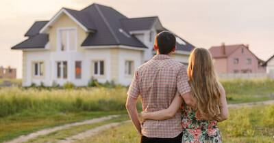 Young couple holding each other in front of their new house. Life Stage Envy pbs rewire