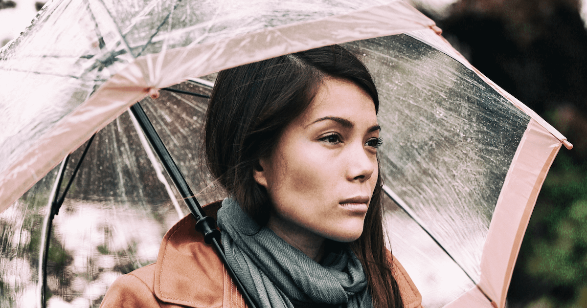 Young depressed woman under her umbrella. Seasonal Affective Disorder pbs rewire