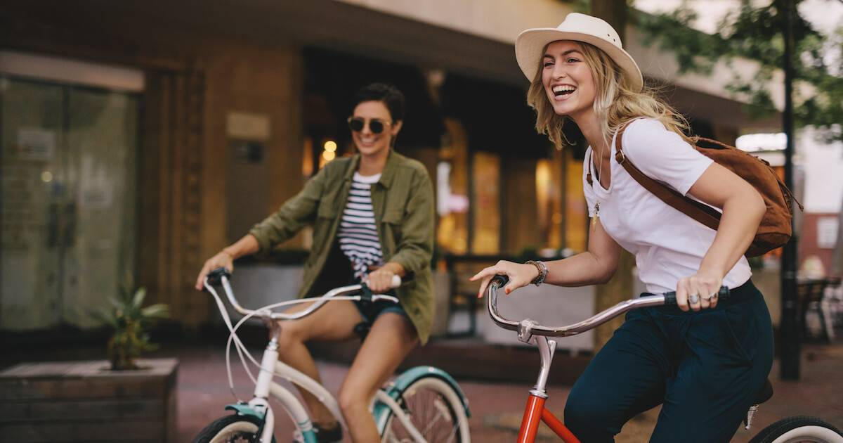 Two young women riding bicycles in the city. Find Friends pbs rewire