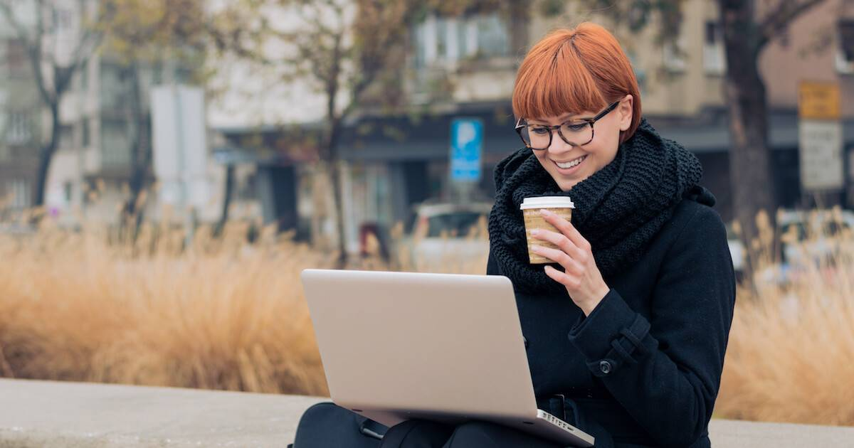 Young woman with red hair working on her latop outside while she enjoys a cup of coffee. Remote Work pbs rewire