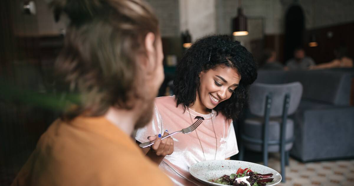 Young African-American woman looking at her food with hesitation. Uncomfortable pbs rewire