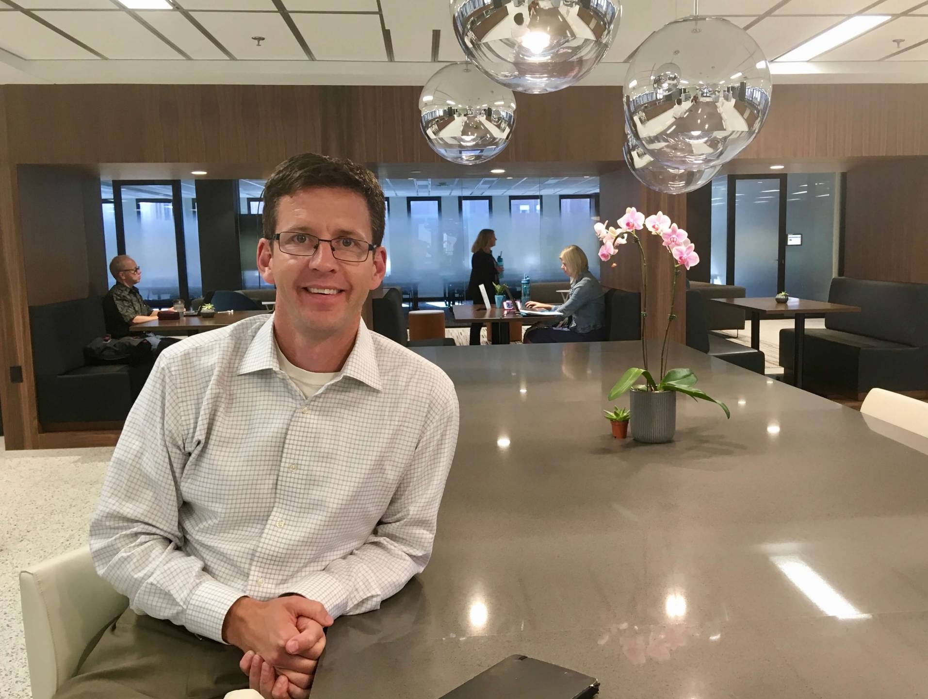 Structural CEO and co-founder Scott Burns, a man in a button down shirt and glasses, sits at a large table. Rewire PBS Work Workplace social network