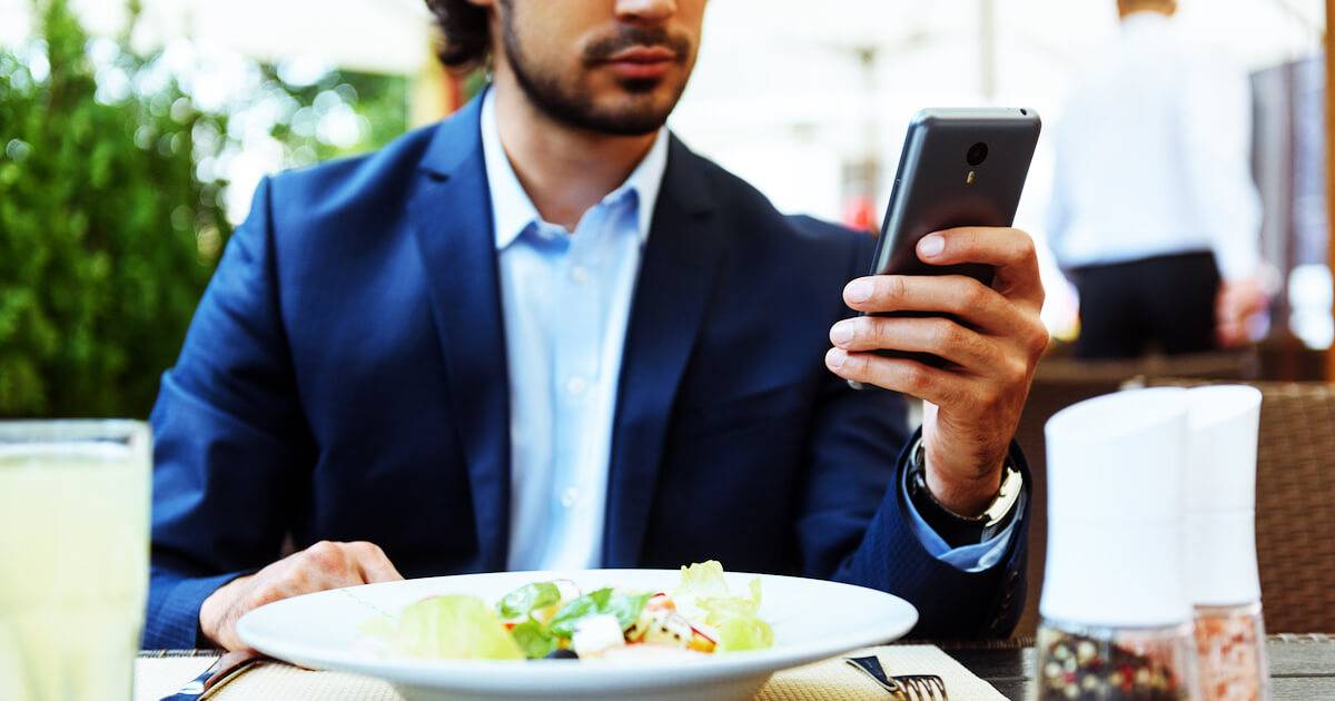 Business man on his smartphone at lunch. Using Email Wrong pbs rewire