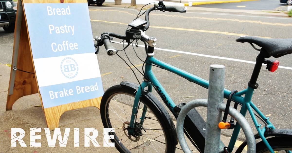 Bicycle resting by Brake Bread sidewalk sign. Community Bakery pbs rewire