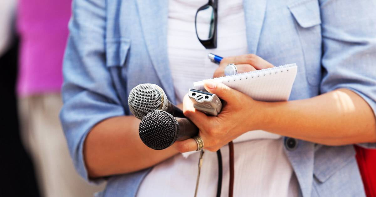 Young female journalist waiting with microphones to interview someone. Journalists pbs rewire