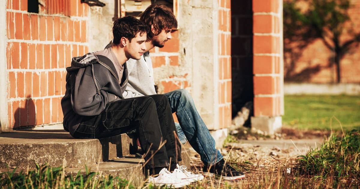 Two younger men sitting on a stoop depressed. People's Feelings pbs rewire