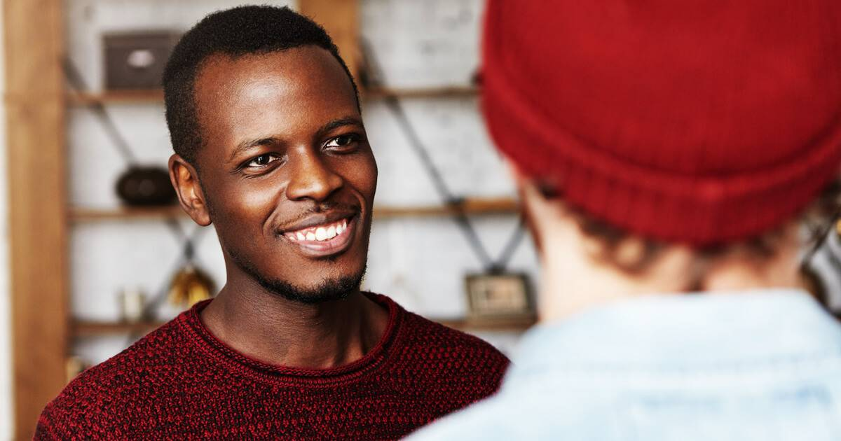 African-American man smiling while talking to his friend. Talking About Yourself pbs rewire