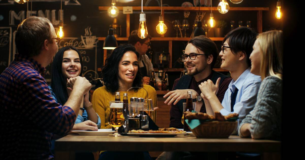 Group of friends at a bar talking about lifestyle differences. pbs rewire