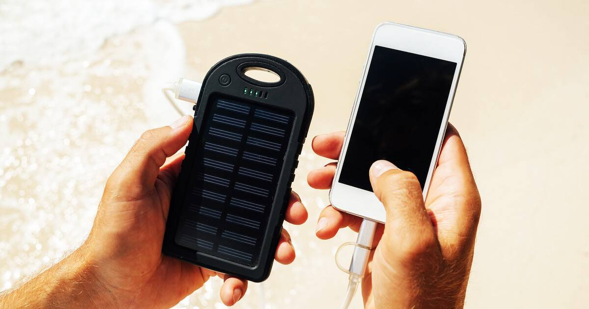 Man holding his smartphone and a solar charger on the beach. Solarpunk Movement pbs rewire