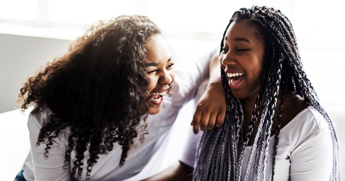 Two African-American sisters laughing together. Sibling Relationships pbs rewire